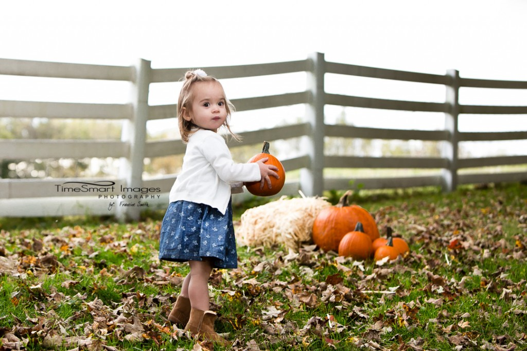 Toddler girl, fall leaves and pumpkins